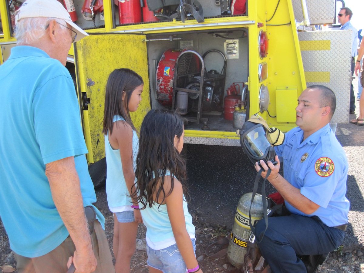 Keiki learn the ins and outs of firefighting equipment from local HFD firefighters.
