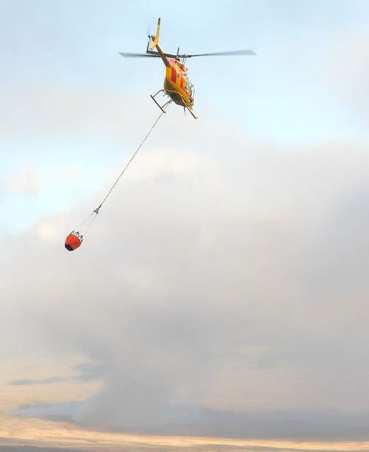"""A Hawaii County Fire Helicopter makes a water drop on a brush fire in Parker Ranch on Friday afternoon. Laura Shimabuku/West Hawaii Today"""