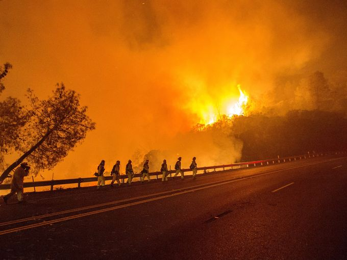 CalFire firefighters walk along Highway 20 as the Rocky Fire burns near Clearlake, Calif. The fire has charred more than 27,000 acres and is currently only 5% contained.   Josh Edelson, AFP/Getty Images