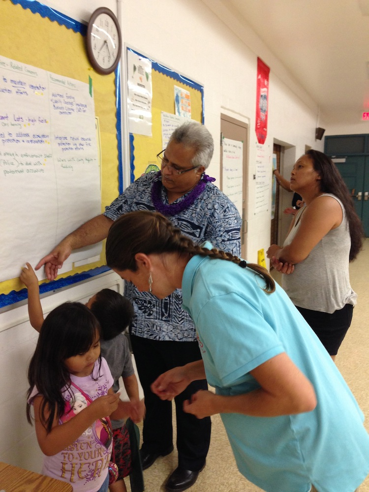 Councilman Kualii and keiki review input collected to decide which items to prioritize.