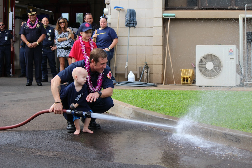 """Trucker Dukes shooting water with his dad, firefighter Joshua Dukes outside of the Kahului Fire Station. Photo by Wendy Osher."""