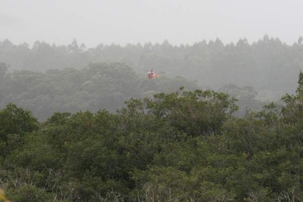 """COLIN M. STEWART/Tribune-Herald A Hawaii County rescue helicopter returns after making several water drops above the wildfire in Laupahoehoe Tuesday afternoon."""