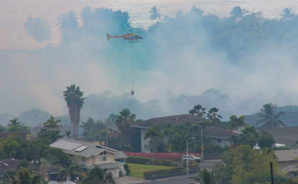"""A Hawaii County helicopter performs a water drop on a brush fire that threatened homes in the Komohana Kai subdivision of Kailua-Kona on Wednesday. (Photo courtesy Denny Miller/Special to West Hawaii Today)"""