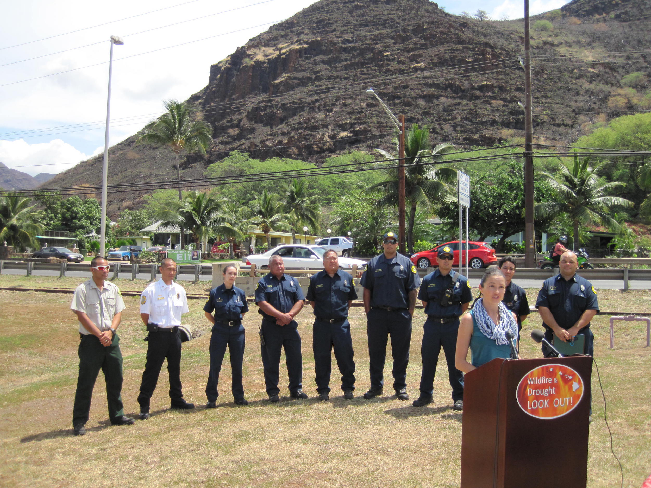Elizabeth Pickett (HWMO) speaks to media with Oahu firefighters standing behind her. In the background: the charred landscape of Nanakuli from the recent fire.