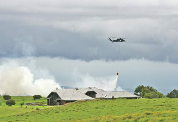 """An Army UH-60 Blackhawk drops water on a fire near Waikii Ranch on Monday afternoon. The crew came from the medevac team."" (Graham Milldrum / West Hawaii Today)"