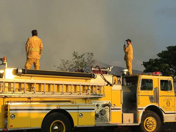 """""""Firefighters survey the scene at mile marker 15 on Thursday afternoon."""" (Laura Ruminski/West Hawaii Today)"""
