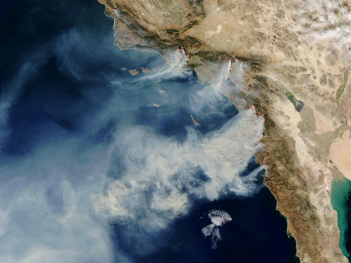 """More than 10 wildfires burned over 200,000 acres in Southern California in October 2003, many of them started by humans. This satellite image shows strong winds carrying smoke over the Pacific."" Credit: MODIS Rapid Response Team/NASA"