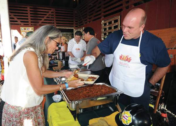 PTA Fire Chief Eric Moller serves their recipe to Connie Bender at the Chili Cook-Off for Wildfire Prevention Saturday at the Parker Ranch Red Barn. (Laura Ruminski-West Hawaii Today)