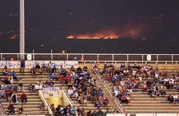 """Football fans at War Memorial Stadium watch a game Thursday night while a brush fire lights up Central Maui and blackens former sugar cane fields. The blaze was fully contained at 2:03 a.m. Friday. It consumed about 100 acres. A cause had not been determined as of Friday night. -- The Maui News / MATTHEW THAYER photo"""