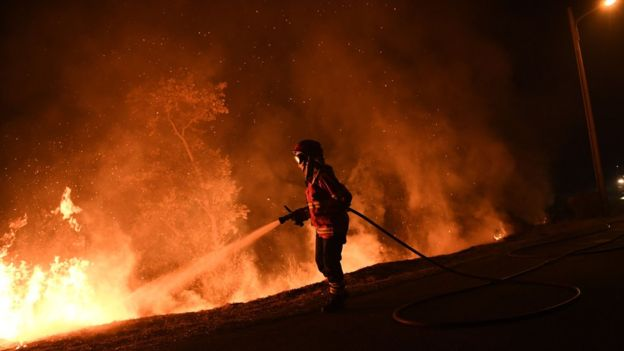 """Fires continued into Monday night, despite rainfall in some affected areas."" Credit: AFP"