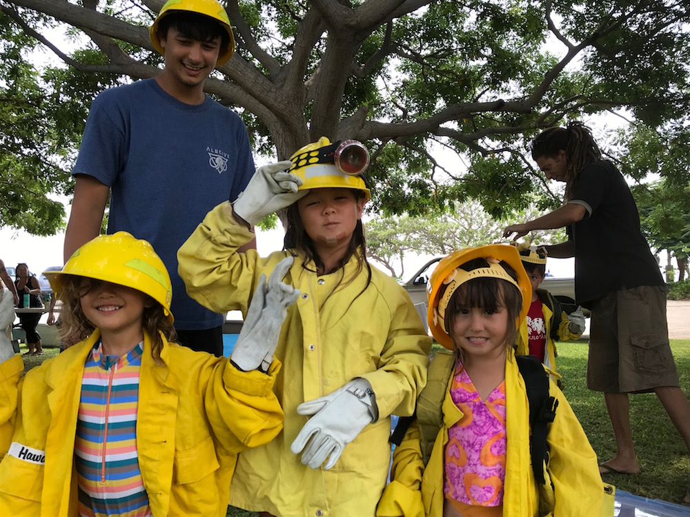 Keiki having fun dressing up as wildland firefighters at Na Kilo Aina Nohona.