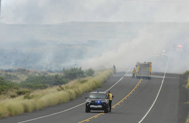 """Firefighters battle a fire on Ane Keohokalole Highway near Palamanui Tuesday afternoon."" (Laura Ruminski/West Hawaii Today)"