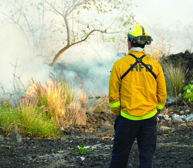 """A Hawaii County firefighter monitors a brush fire."" (Laura Ruminski/West Hawaii Today)"