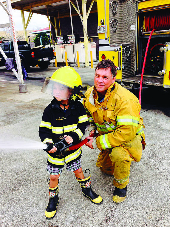"""David Mahon helps his son, Dylan, use a fire hose in this family photo. (Chris Anderson/Special to West Hawaii Today)"""