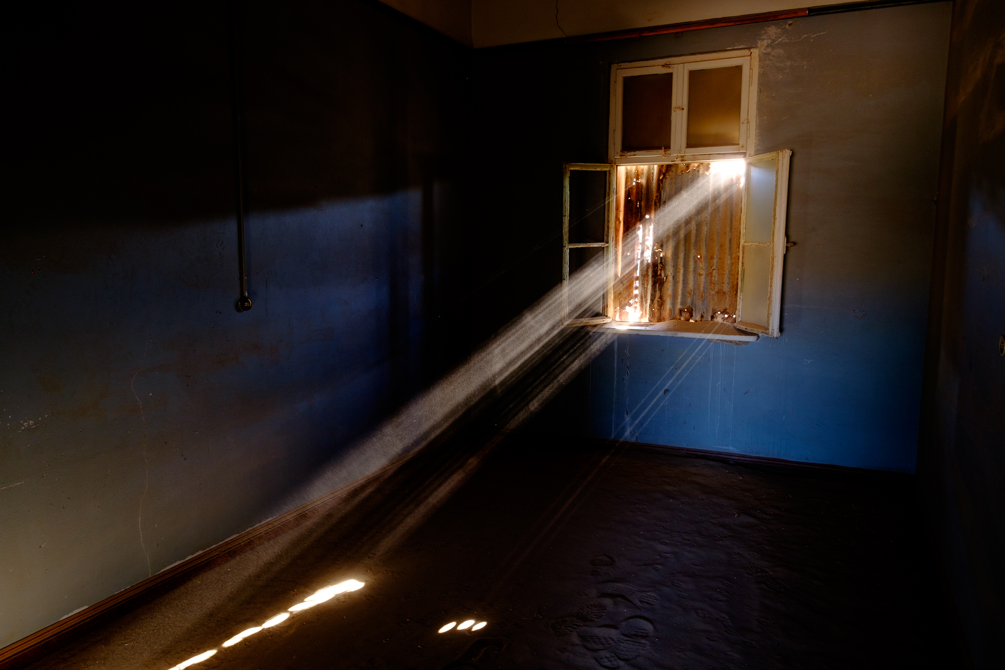 Light beams through rusted iron boarding up the window of this room in the school