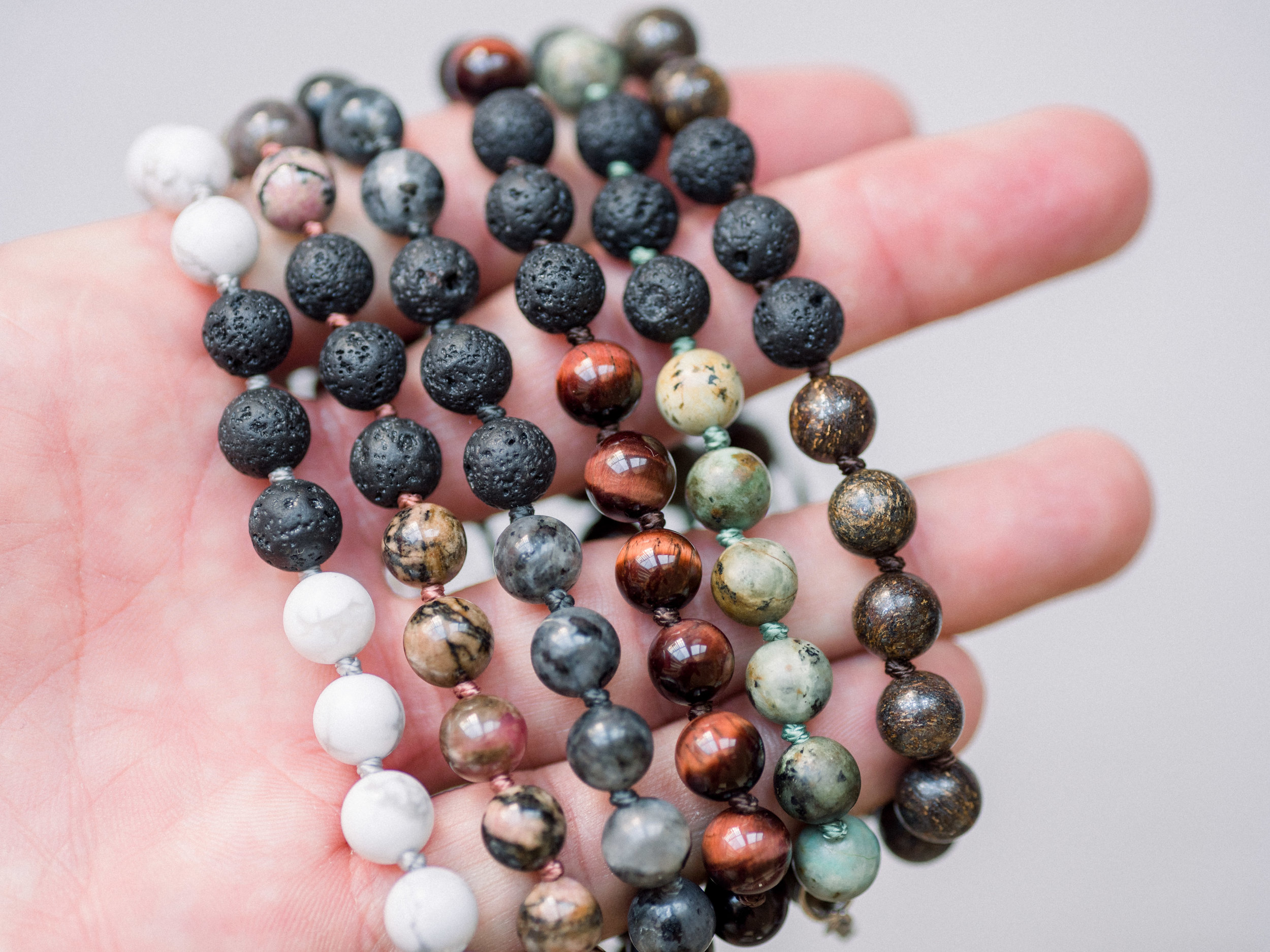 From left to right: White Howlite, Rhodonite, Larvakite, Red Tiger's Eye, African Turquoise + Bronzite.