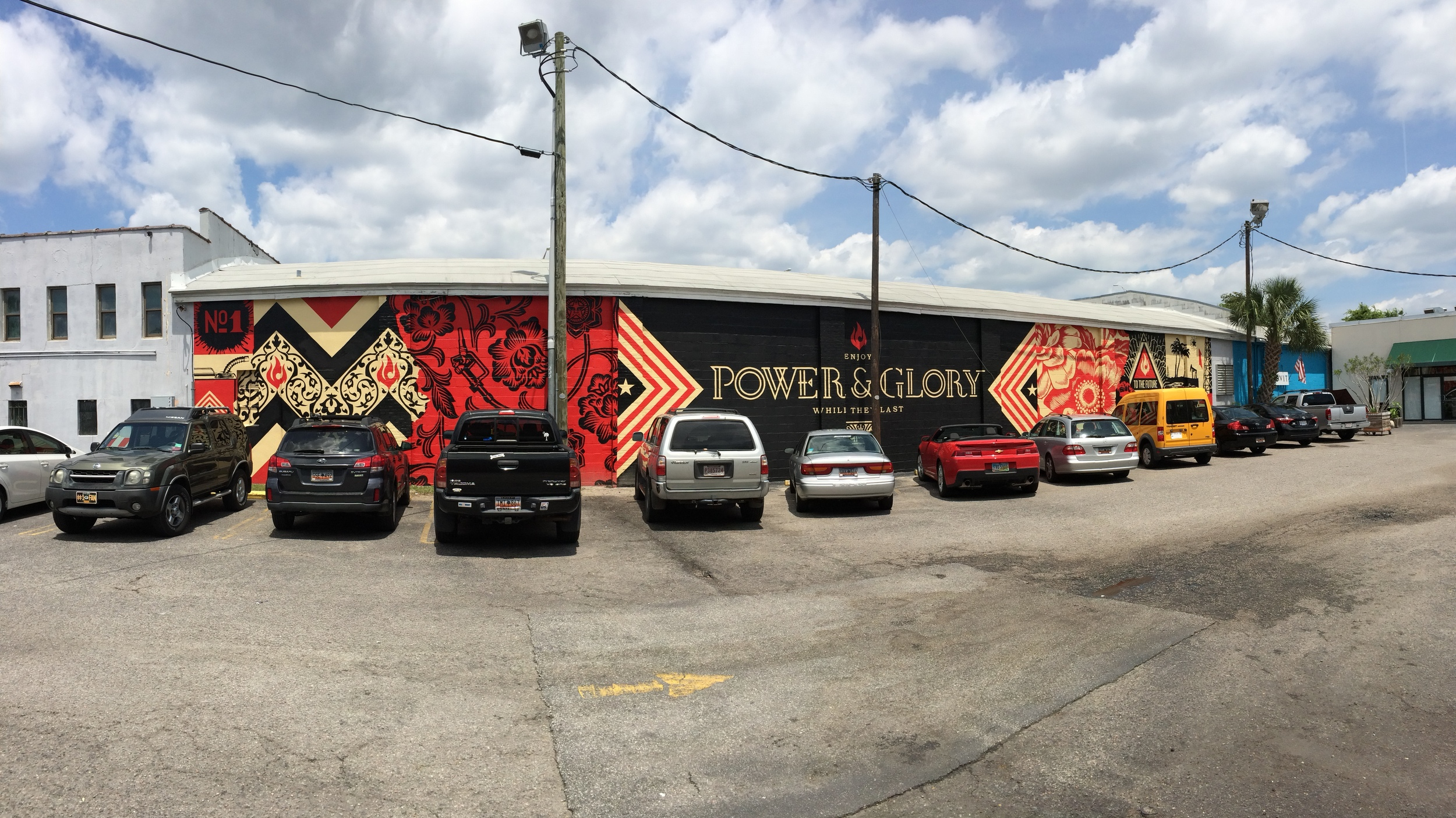 Power & Glory mural lining the parking lot outside of Butcher and Bee