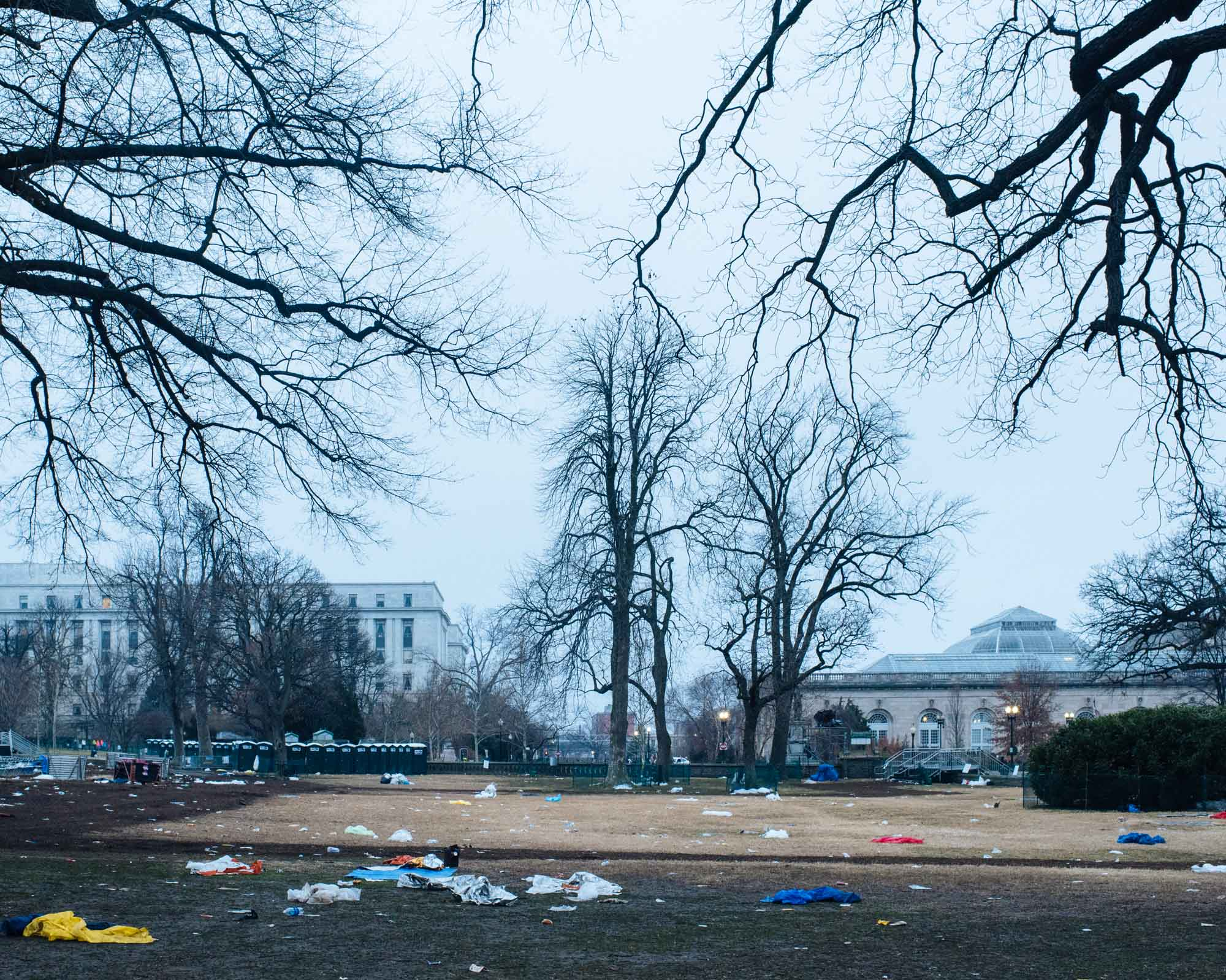 The lawn in front of the Capitol is covered with trash.