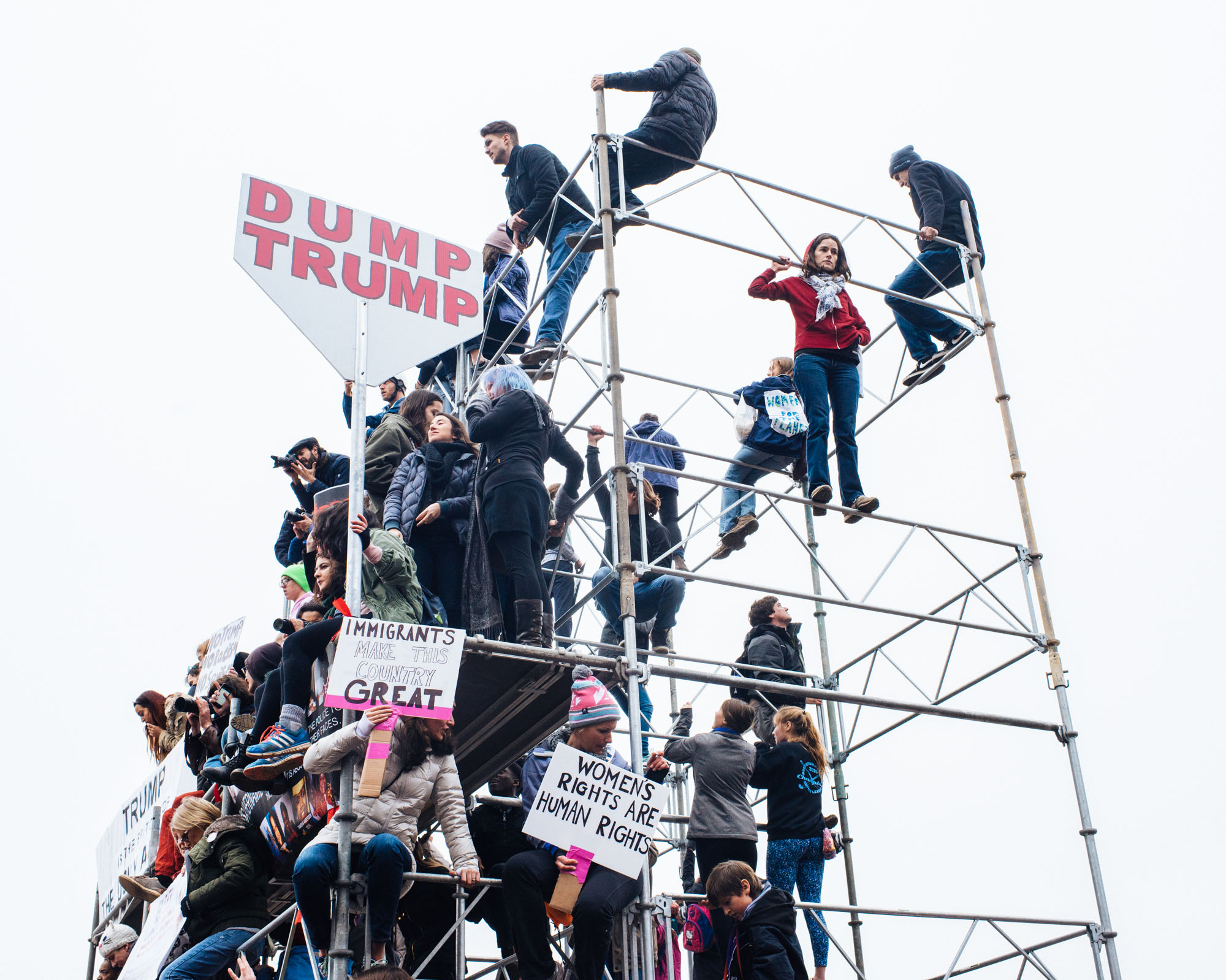 Protesters climb on a steel construction on the Mall for a better view of the hundreds of thousands of people.