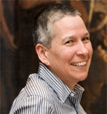 Photo of Susan Dion, in 3/4 profile, smiling and wearing a blue and white striped collared shirt.