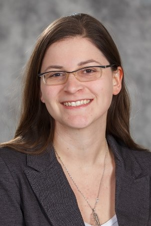 A head and shoulders headshot of Jen Rinaldi, a white woman with brown hair, wearing glasses and a grey blazer, smiling at the camera.
