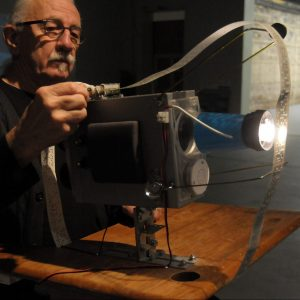 A white man with long white hair a white mustache, wearing black framed glasses and a black t-shirt is sitting at a vintage wooden desk. He is looking at a grey object with a light and a narrow strip of paper and his hand is on top of the object.