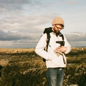 A photo of Colin taken in Northern Ireland. Dark clouds over the ocean and rocks are in the background. Gazing downwards, he is wearing a warm hat and jacket, holding a video camera.