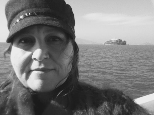 Black and white photograph of a fat white woman close up and face on. The backdrop is grey water and sky and there's a small island in the distance. The woman's dark eyes look directly at the camera and her smile is subtle. She wears a dark brimmed cap and a fluffy, wooly sweater. Her long hair blows in the wind.