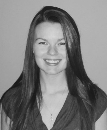 Black and white photo of Angela Underhill. She is smiling and facing the camera. She has long hair.