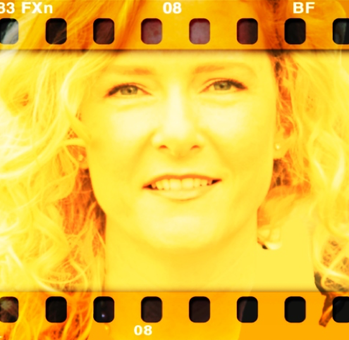 Image of Allison Crawford that appears to be film; she is yellow in the photograph and looking directly at the camera.