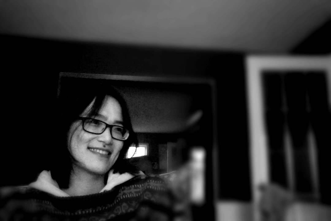 Black and white photograph of Lilith Lee, looking away from the camera. She has black-framed glasses. She is smiling.