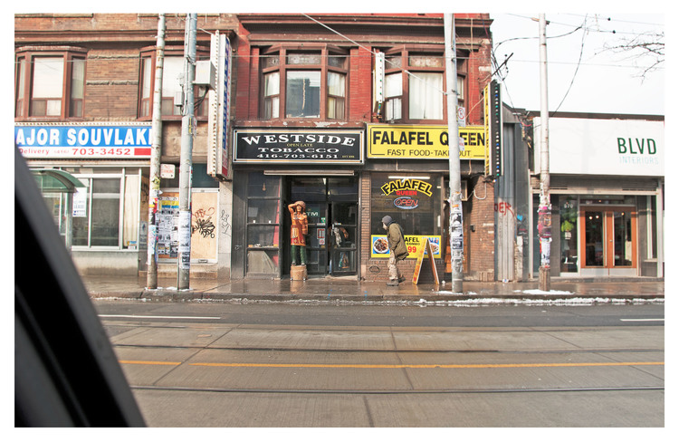 Toronto, Ontario, drive-by view of Cigar store Indian and street person, Queen St and Bathurst
