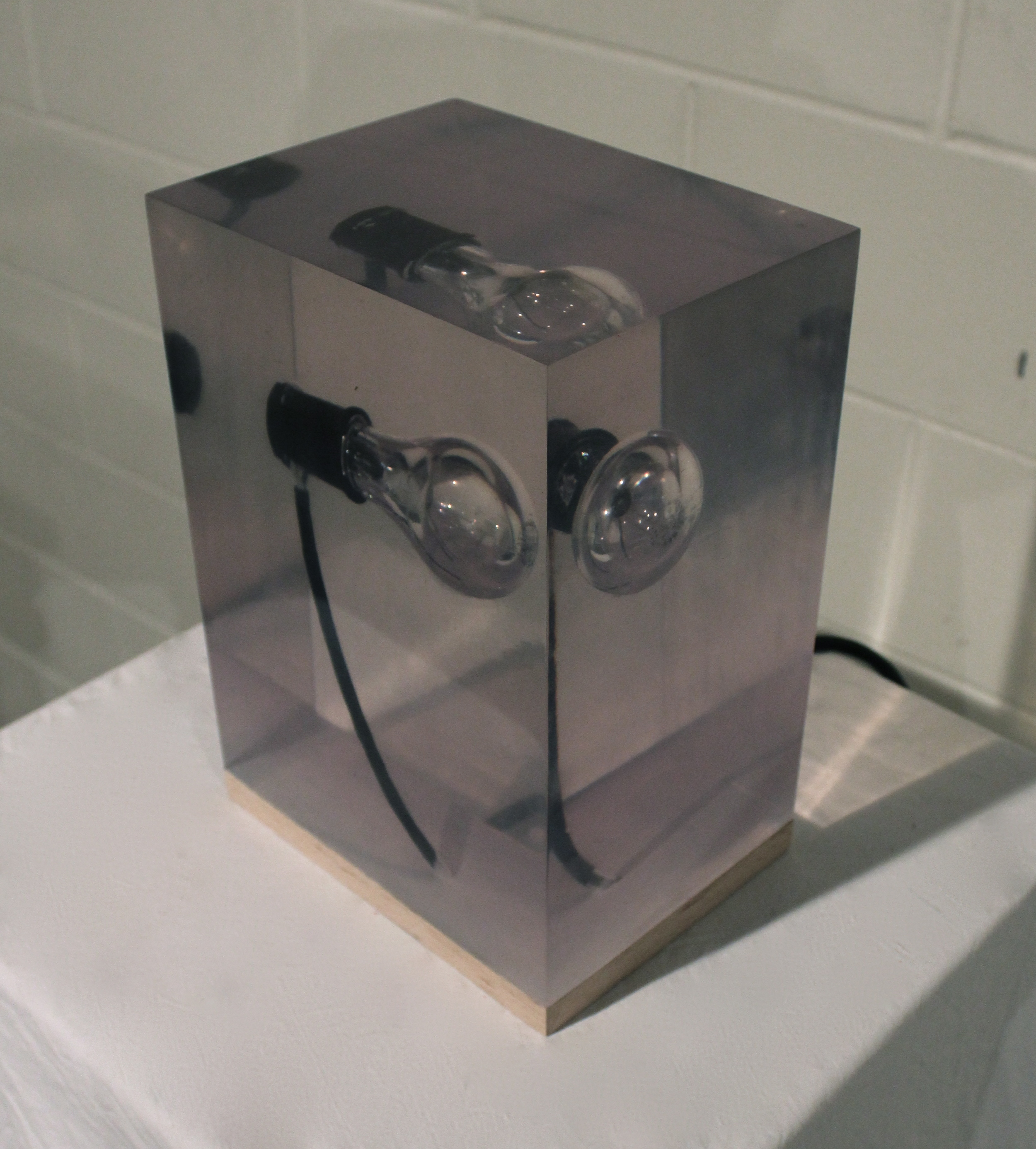 Off On Off. 2011. Cast and polished polyester, lighbulb, electrical cord, oak base.