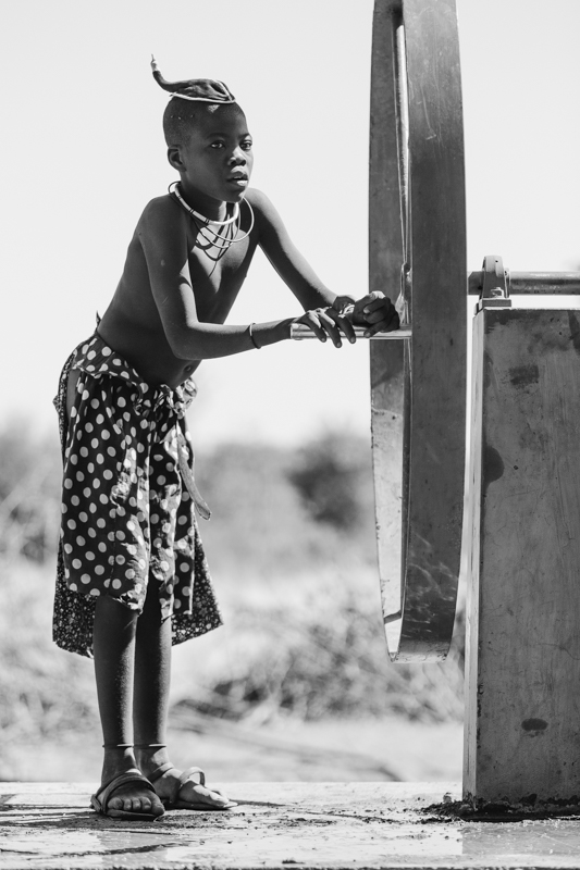 A young Himba boy pumps water from a well, which he will then carry home in drums to his village.  Onconcua, Cunene Province   ©24Atlantic