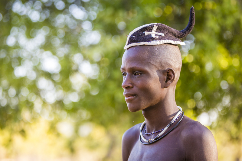The prime of his life... Himba boy entering adulthood wears his hair in a simple braid to the back of his head. This will be covered by a turban once he is married.  Soba, Cunene Provence ©24Atlantic
