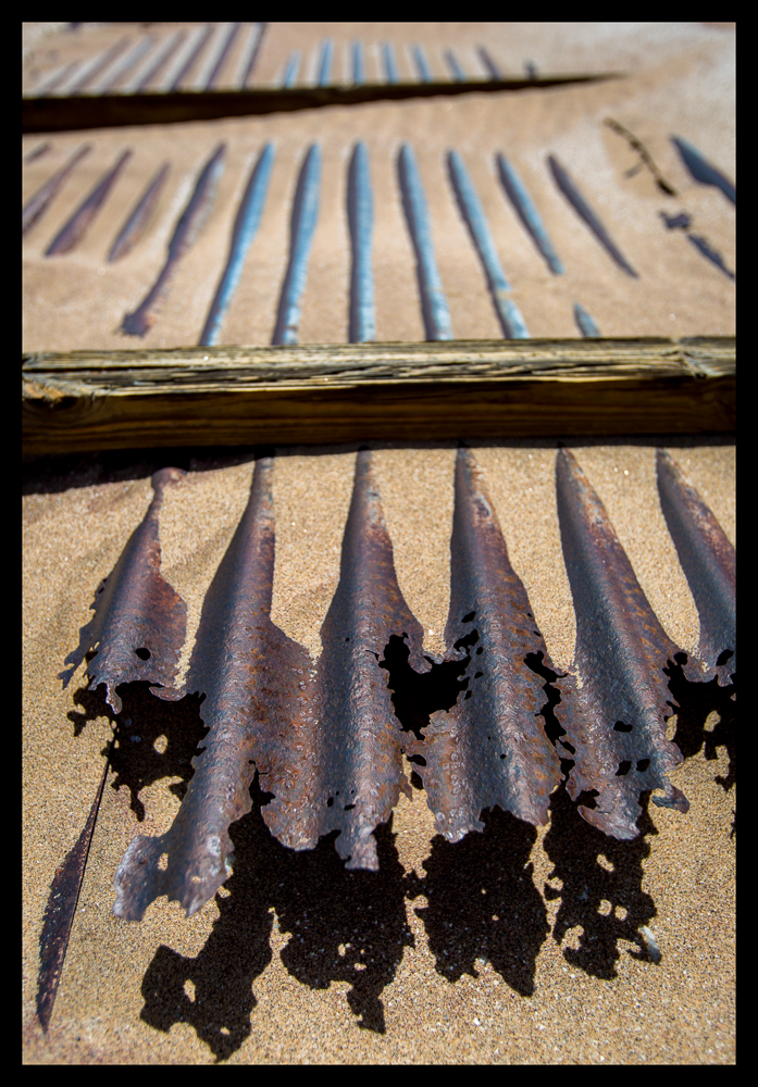 Corrugated iron roofing, blown off housing structures, now making laced patterns and shadows after attacks from the never-ending winds and sand particles.