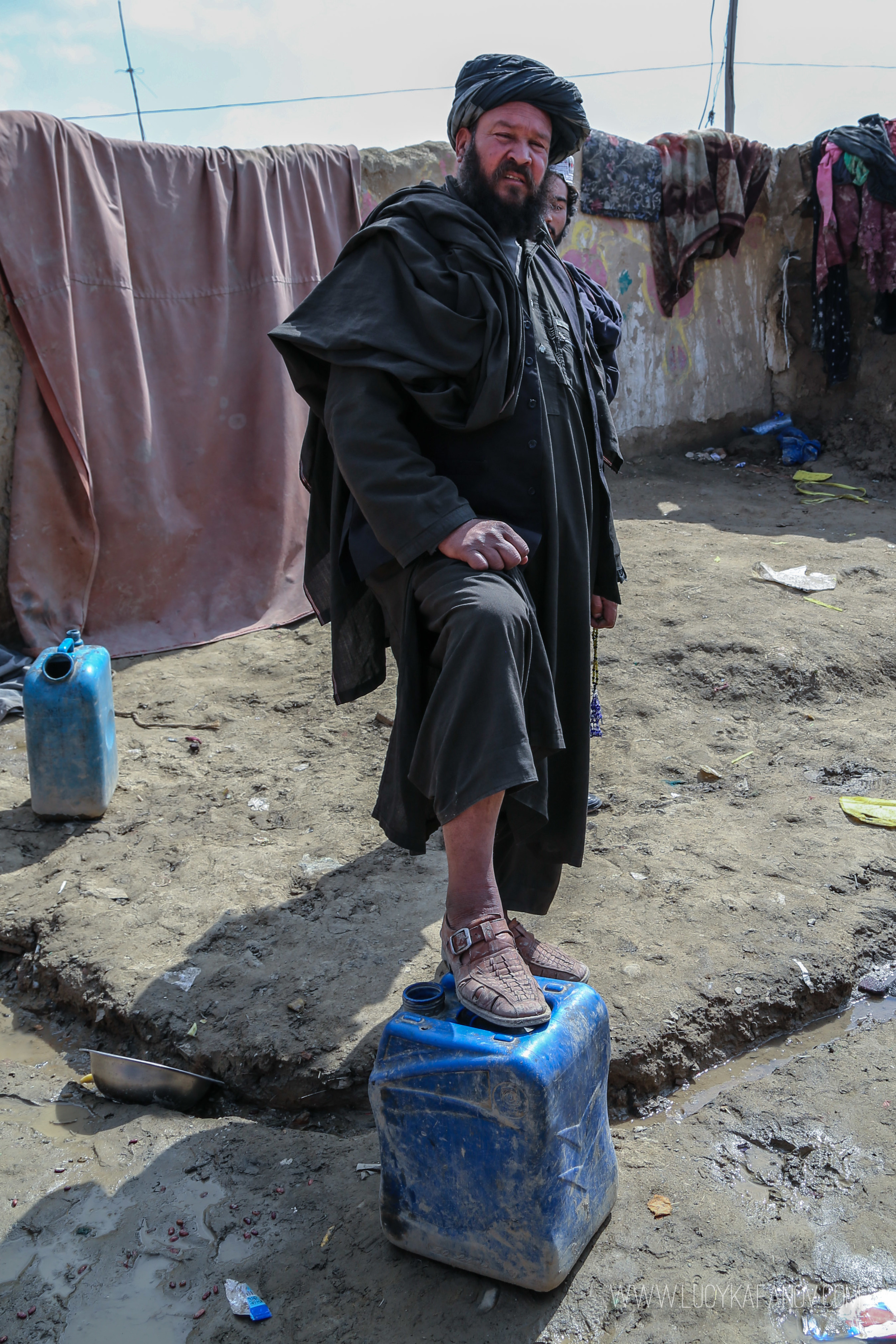 A man stands proudly in his courtyard at this IDP camp on the edge of Kabul. In his native Helmand province he had land. Here, just the mud and little else.