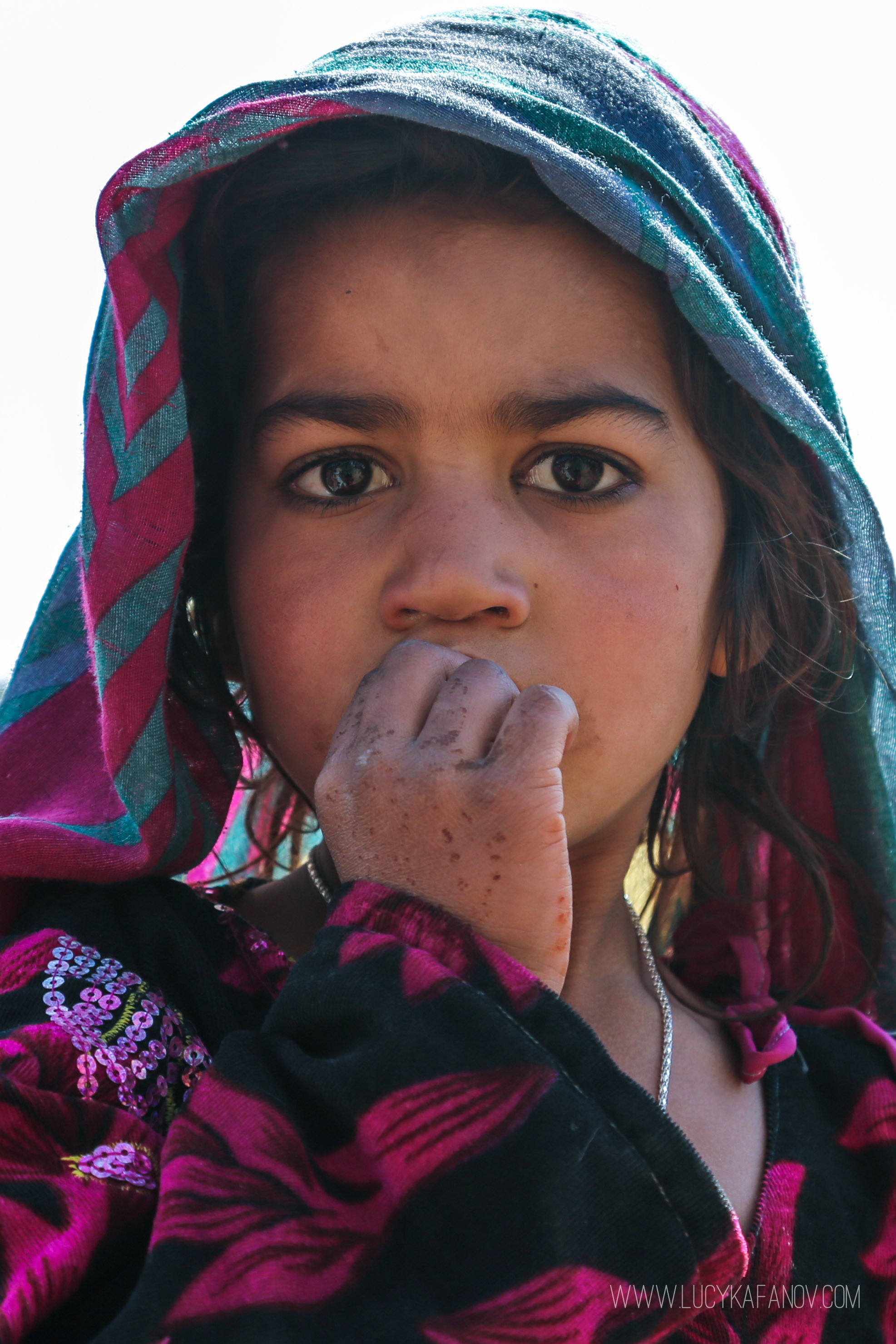 A young Afghan girl stares back into my camera.