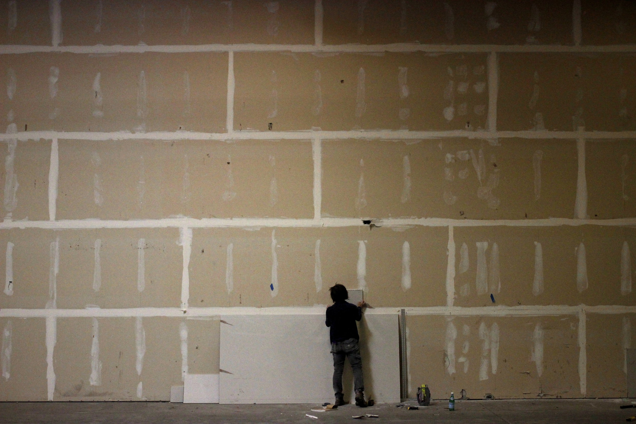 Repairing damaged drywall in a giant warehouse.