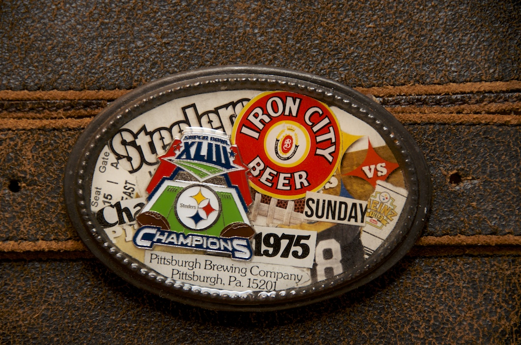 """Hey NFL lovers! There's no greater fan than a Patriots fan. Unless you're a Packers fan. Or a Cowboys fan. Or a...well, you get the idea.    A Steelers fan met Vintage by Cathy at an arts festival. She asked if we could custom make a buckle that would suit her all-things-Pittsburgh-obsessed personality.    Of course the answer was, """"YES!"""" We pieced together her memorabilia.  Maybe this Vintage by Cathy custom belt buckle will replace the fan's beloved, """"Terrible Towel"""" for the 21st century!"""