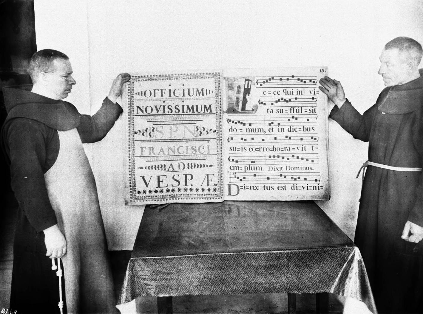 Monks displaying an illuminated score at Mission Santa Barbara, California, ca.1904