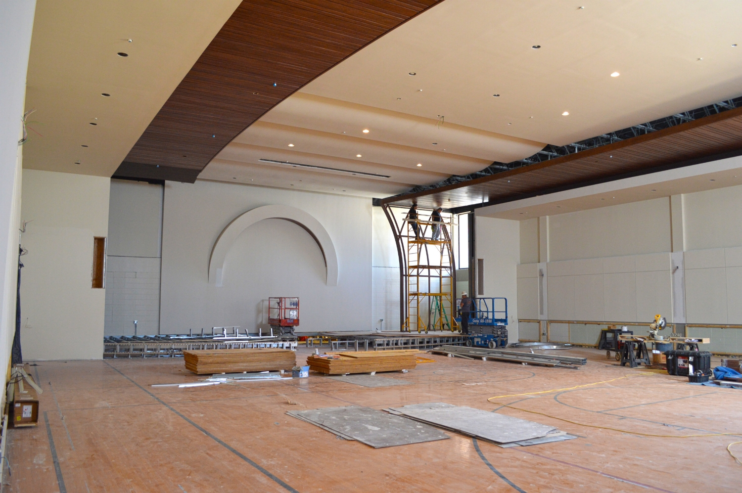 Workers install a wood slat screen wall on the Sanctuary stage. The mission style arch speaks to the local architectural flavor.