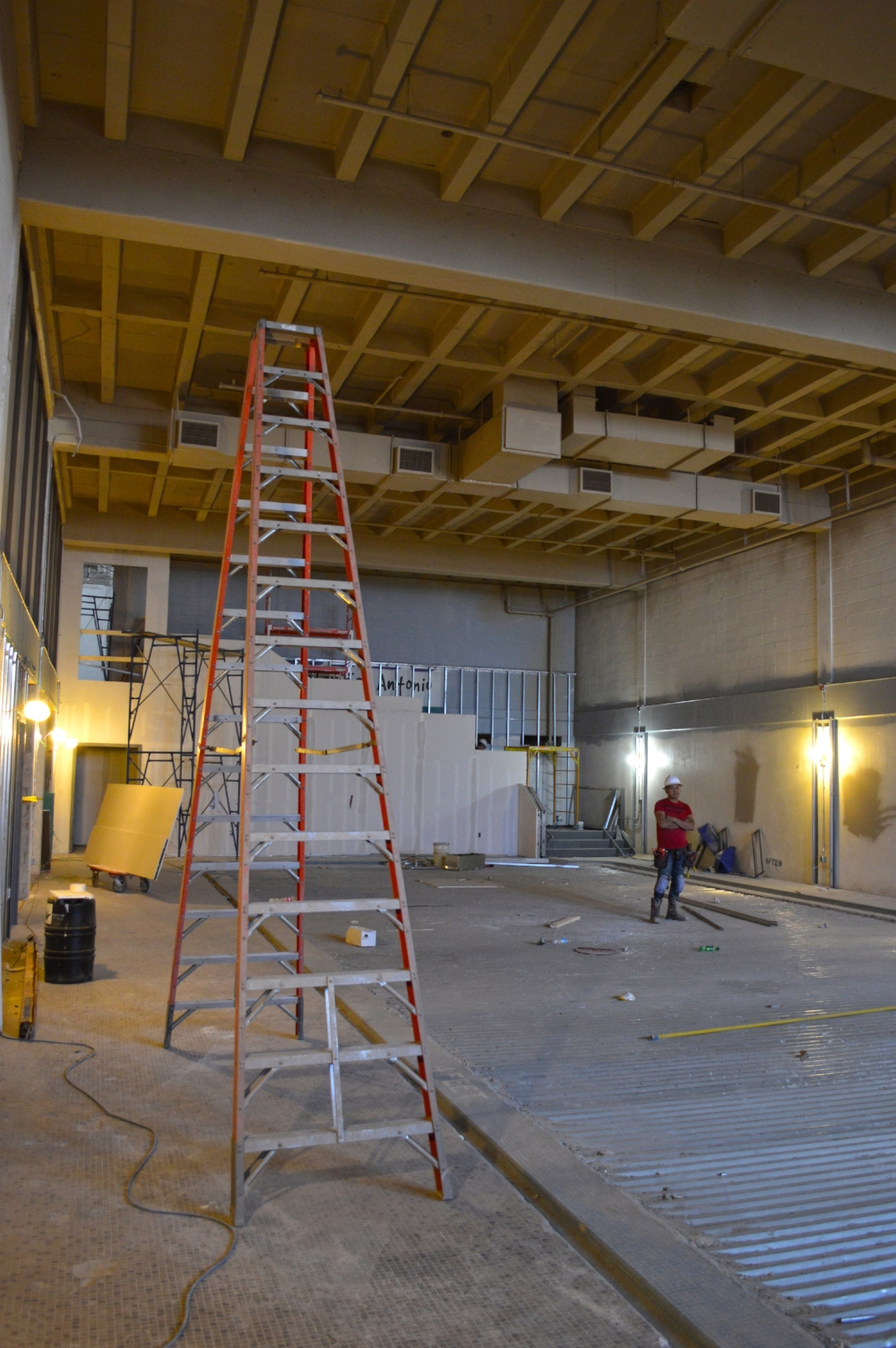 The old swimming pool has been covered over with metal decking in anticipation of the new floor which will make this room the Fellowship Hall. Old ceiling tiles were removed to expose the cast-in-place concrete roof structure.
