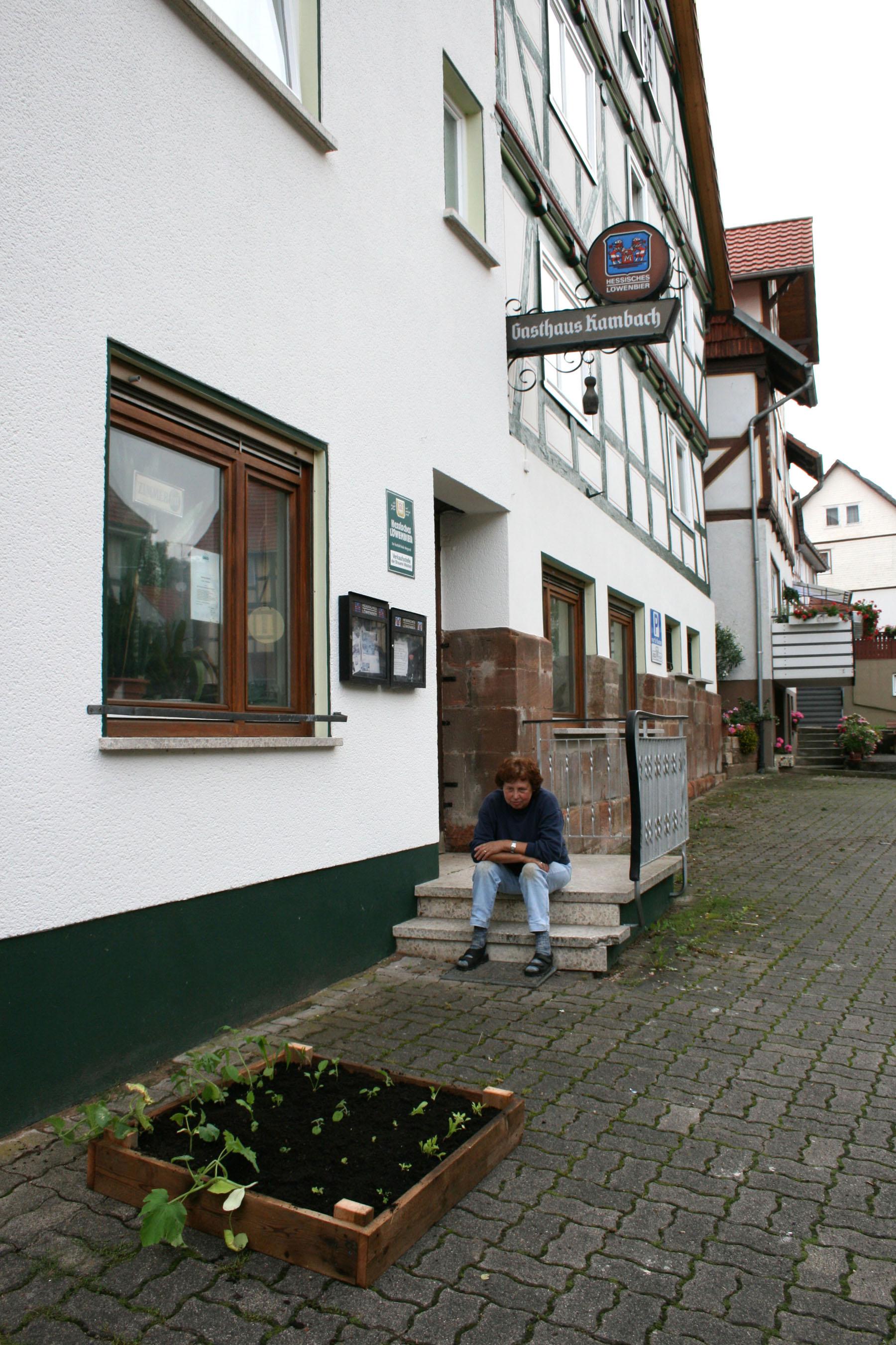 """Gaststätte Kambach,Zur Kirche 1,  36211 AlheimOberellenbach,    Uiteindelijk gaat de twaalfde volkstuin naar kunstenaar Gerd Logemann's Godmother. Zij heeft een pension. Terwijl ik het tuintje maak kijkt ze toe. Ik vertel dat haar plaatsgenoot Michael er ook een heeft. """"Oh die heeft het veel te druk"""" zegt ze. """"Ik zal ook wel op zijn tuintje letten"""". Kijk, dat is nou het goede dorpstuin gevoel!     E-mail; 29 november 2007:Ich bin die Tochter von der Frau Kambach. Ich soll Ihnen den Brief und die Bilder Ihres Projektes übersenden. Leider konnte ich die Bilder est nach dem ersten Frosttag machen, da ich nicht so oft dort bin. Aber ich kann Ihnen versichern das der """"Garten"""" wunderschön geworden ist.      Herzlichen Dank für Ihren Brief und das Foto. Ich kann Ihnen mit Stolz versichern,daß mir Ihr """" Schrebergarten"""" viel Freude bereitet hat. Auch unsere Nachbarn habe das Wachstum mit Interesse verfolgt. Mittlerweile ist der Garten ganz zugewachsen. Ich habe Gurken und Mangold geerntet und eine Zuchini gab es auch. Beim Salat hatte ich leider unbekannte Helfer. Es sei Ihnen gegönnt :-) Ich habe roten Mohn ausgesäht, der schon fleißig gewachsen ist, für die Blüte im nächsten Jahr. Ich denke auch dann werden wieder viele ihre Freude daran haben."""