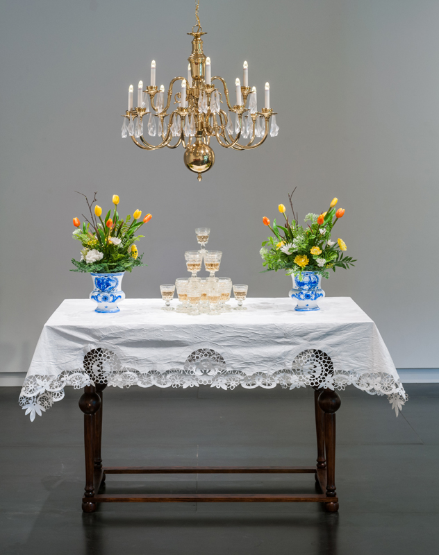 Drink , 2016 Brass chandelier with fruit-bat crystals, 17th century-Dutch-style table, Tyvek® table cloth, stemware with wine, hand-painted Delftware-style vases with plastic flowers dimensions variable