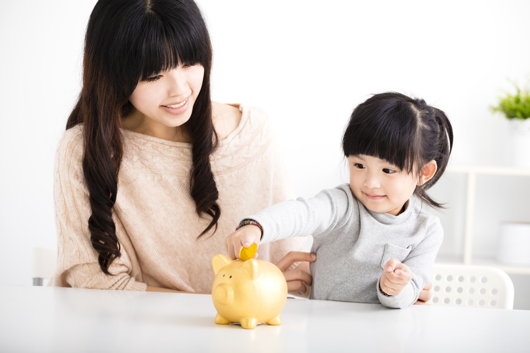 Happy-mother-and-daughter-Inserting-Coin-In-Piggy-bank-000084831365_Medium.jpg