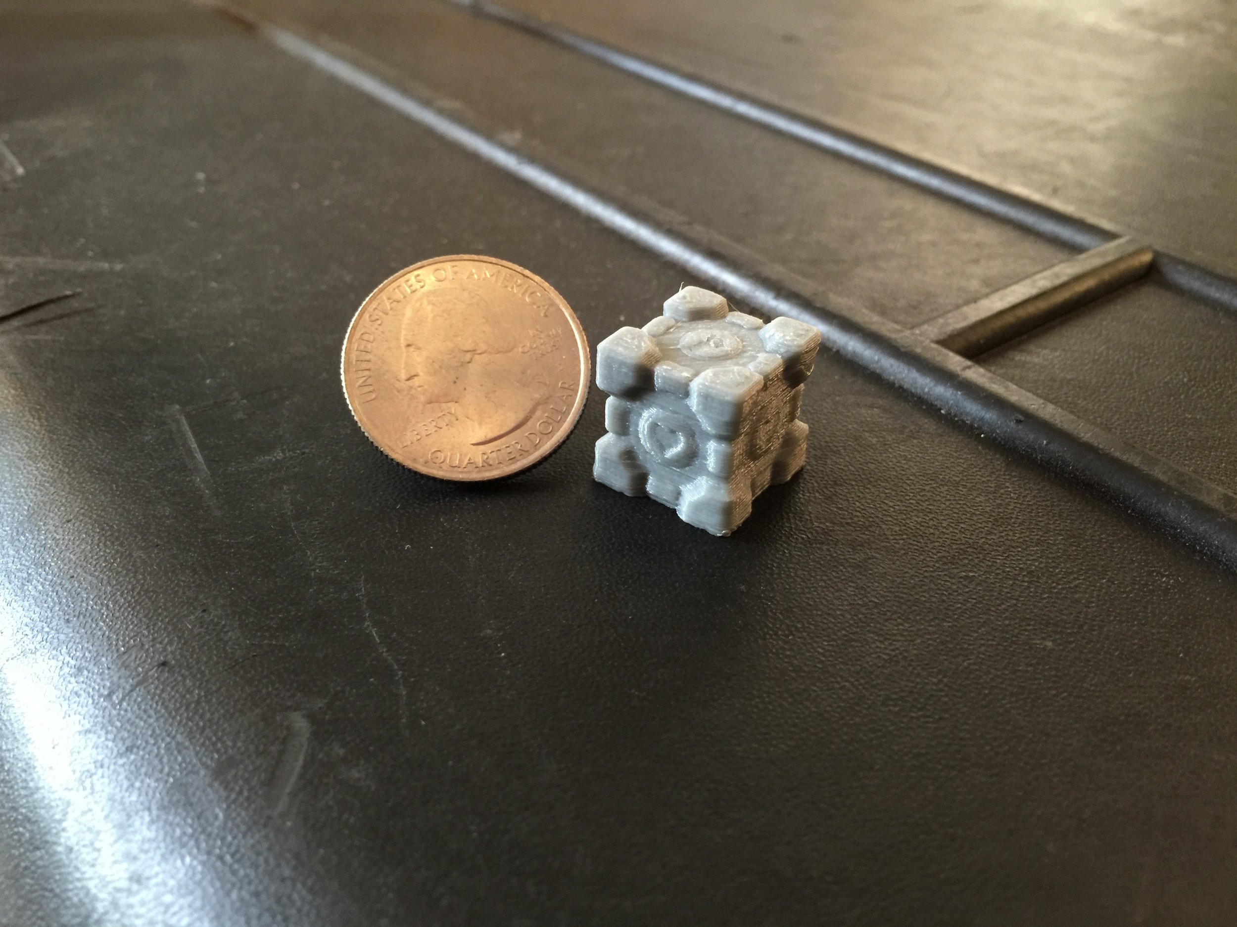 The heart on the side of the gray cube printed clearly but the heart on top is muddled due to the nozzle's relatively large diameter for features perpendicular to the nozzle