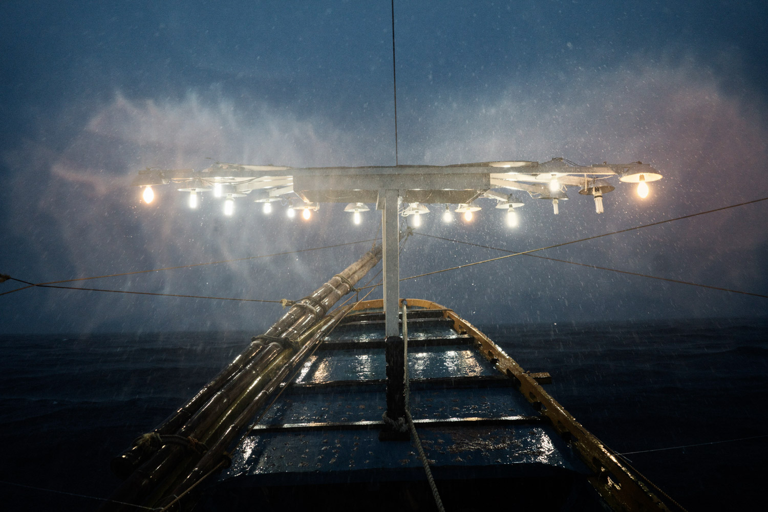 The lights used to attract fish towards the boat are seen during a storm on 'Melissa' - a 15.53 gross ton basnig fishing boat - while they head out to fishing grounds in national waters close to the South China Sea, from Quezon, Palawan, The Philippines on June 27th, 2016.