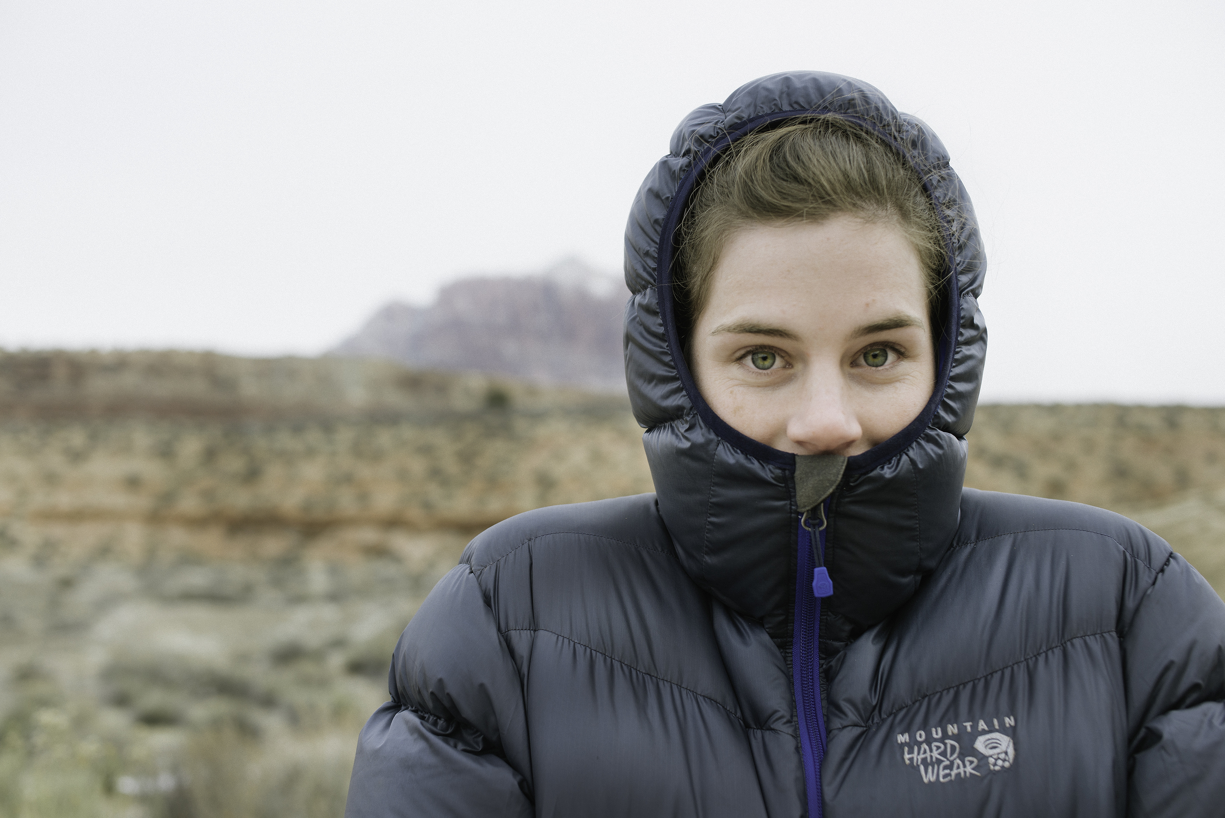 Skye shielding her face from the cold wintery breeze on the Smithsonian Butte, Utah