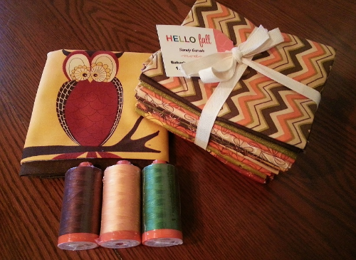 Fabric Bundle has 13 Hello Fall Fat Quarters & Hello Fall fabric panel.  Aurifil Threads  include 3 LARGE Mako Cotton 50 wt spools with 1422 yards ONE (1) each in the following colors 2214, 2360, 2890. Approximate Retail value of prize is $80.00. Contest ends Nov. 4th, 2014.